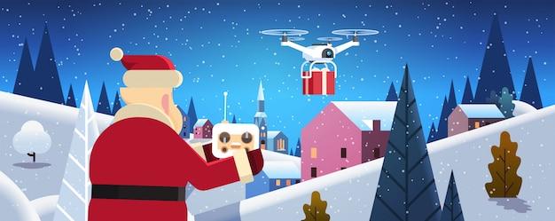 Santa hold contrôleur drone service de livraison pendant la nuit hiver village Vecteur Premium