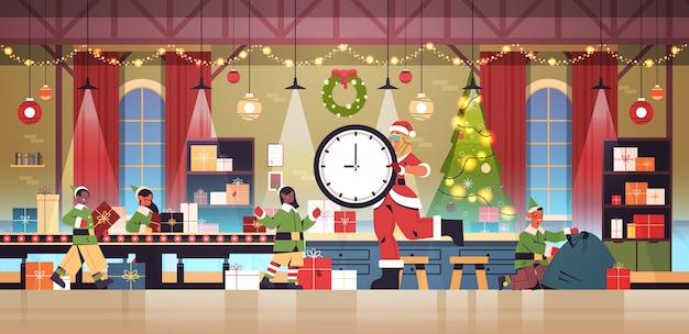 Santa Woman Holding Clock Mix Race Elfes Mettant Des Cadeaux Sur Le Convoyeur Nouvel An Vacances De Noël Célébration Concept Atelier Intérieur Illustration Vectorielle Pleine Longueur Vecteur Premium