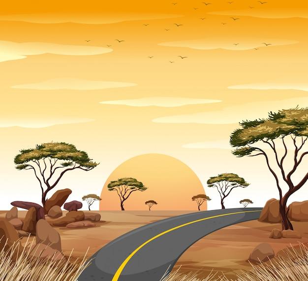 Scène de savane avec une route vide au coucher du soleil Vecteur gratuit