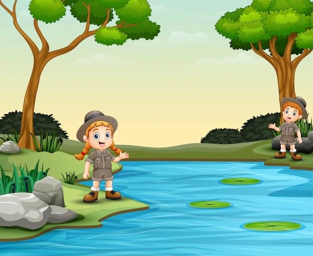 Scout garçon et fille parlant au bord de la rivière Vecteur Premium