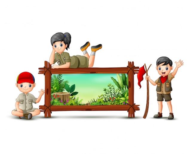 Scout garçon et fille près du cadre en bois Vecteur Premium