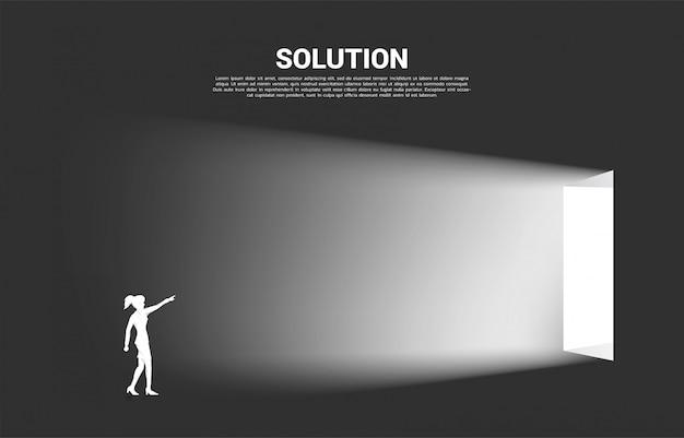 Silhouette de femme d'affaires pointe vers l'avant pour sortir de la porte. concept de démarrage et de solution d'entreprise. Vecteur Premium