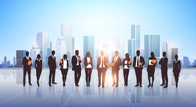 Silhouette de gens d'affaires debout sur la ville moderne Vecteur Premium