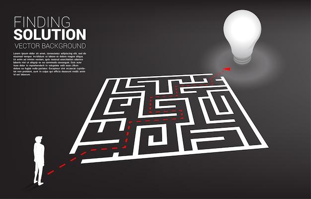 Silhouette d'homme d'affaires avec le chemin de la route pour sortir du labyrinthe à l'ampoule Vecteur Premium