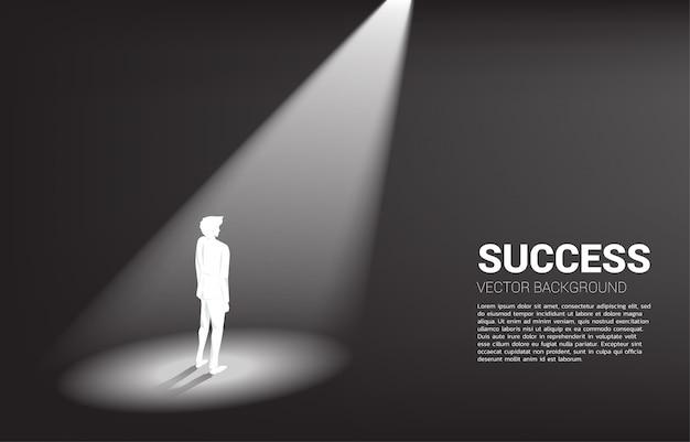 Silhouette d'homme d'affaires debout sous les projecteurs Vecteur Premium