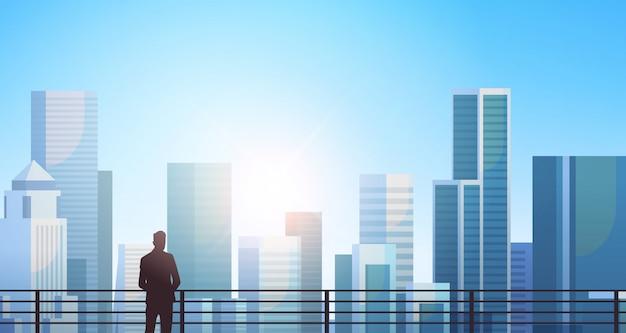 Silhouette d'homme d'affaires debout sur la ville moderne Vecteur Premium