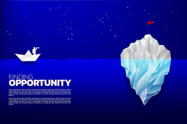 Silhouette d'homme d'affaires avec le télescope sur le navire de papier à la recherche d'indicateur sur l'iceberg. Vecteur Premium