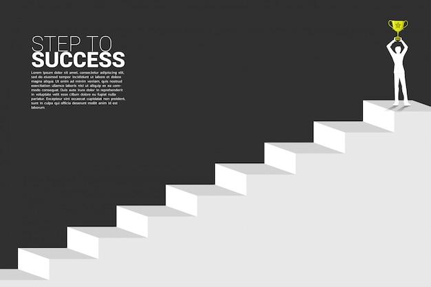 Silhouette d'homme d'affaires avec le trophée du champion au sommet de l'escalier. concept de l'entreprise de croissance, le succès dans le chemin de carrière. Vecteur Premium