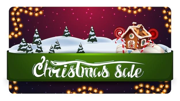 Soldes de noël, bannière d'escompte avec magnifique paysage d'hiver, ruban horizontal vert avec offre et maison en pain d'épice de noël Vecteur Premium