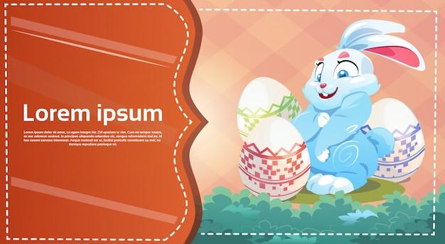 Tenez lapin de pâques décoré carte de voeux de symboles d'oeufs colorés Vecteur Premium