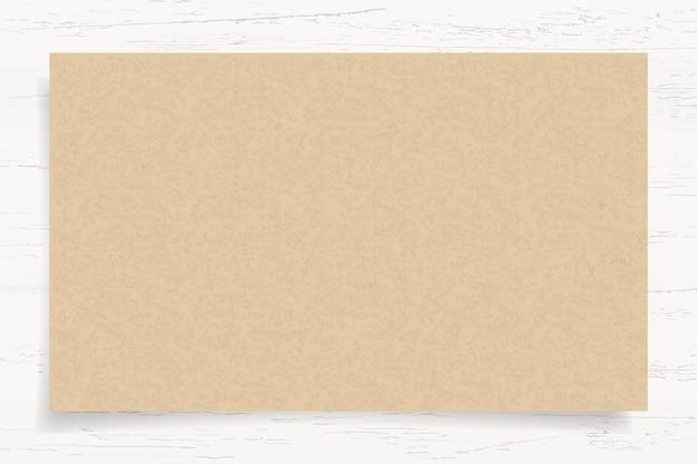 Texture du papier brun sur fond de bois blanc. Vecteur Premium