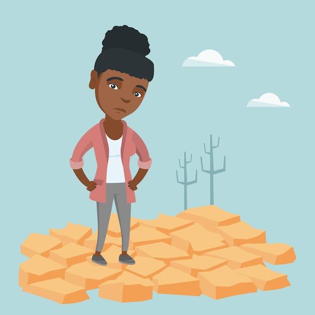 Triste femme debout sur la terre fissurée dans le désert. Vecteur Premium