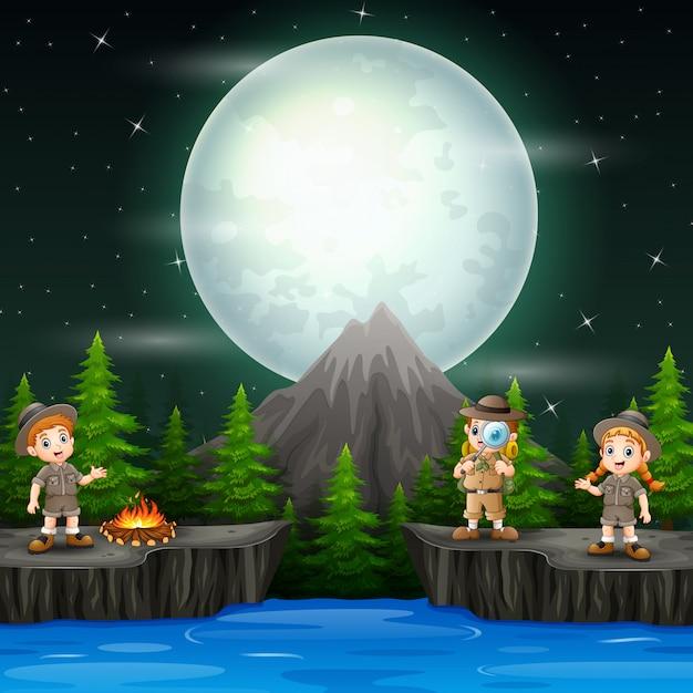 Trois enfants explorateurs avec un feu de camp dans la scène de nuit Vecteur Premium