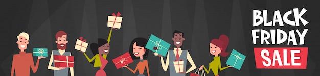 Vendredi noir vente texte sur groupe de personnes détenant différentes boîtes-cadeaux bannière web horizontale Vecteur Premium