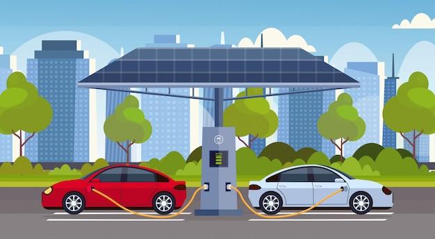 Les Voitures électriques En Charge Sur La Station De Charge électrique Avec Des Panneaux Solaires Renouvelables Respectueux De L'environnement Respectueux De L'environnement De Transport Concept De Paysage Urbain Moderne Fond Vecteur Premium
