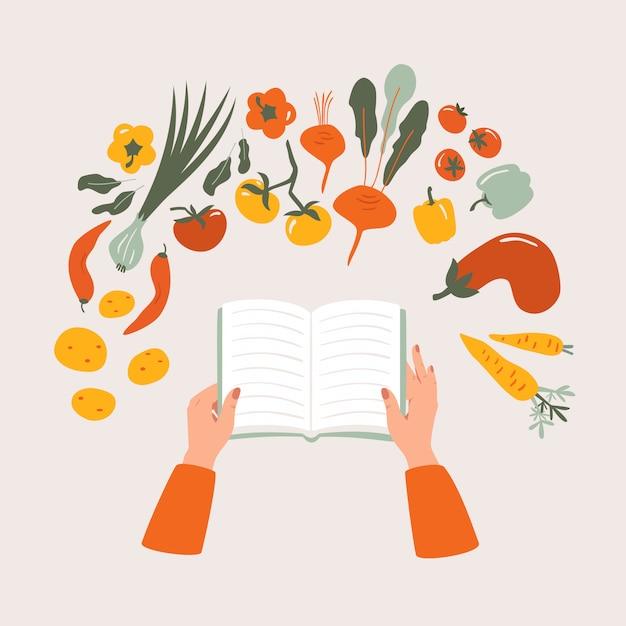 Vue de dessus du livre de cuisine de bande dessinée à la main sur la table entourée de divers légumes. Vecteur Premium