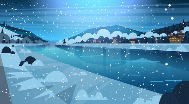 Vue de nuit de rivière gelée avec petites maisons de campagne sur les collines, concept de paysage d'hiver Vecteur Premium
