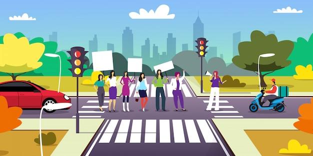 Activistas que protestan en el cruce con pancartas en blanco manifestación feminista movimiento de poder femenino derechos protección concepto paisaje urbano Vector Premium