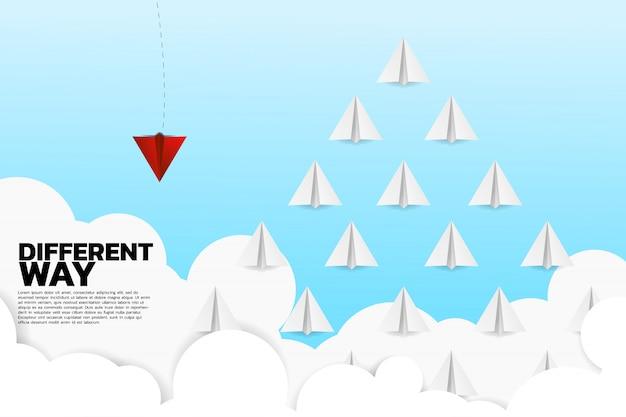 Avión de papel origami rojo va de manera diferente al grupo de blancos. Vector Premium