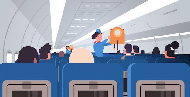 Azafata azafata explicando a los pasajeros cómo usar el chaleco salvavidas en caso de emergencia concepto de demostración de seguridad moderno avión tablero interior plano horizontal Vector Premium