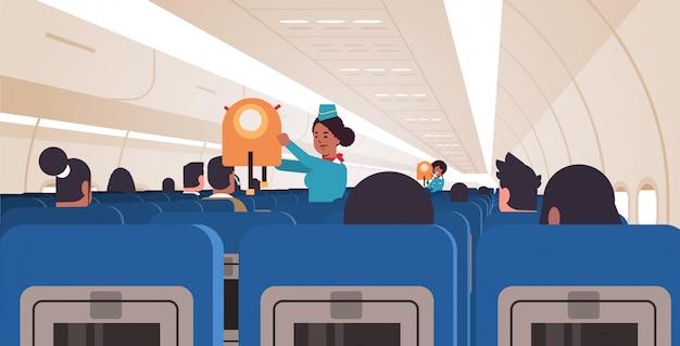 Azafata explicando a los pasajeros cómo usar el chaleco salvavidas en situaciones de emergencia asistentes de vuelo afroamericanos concepto de demostración de seguridad tablero de avión moderno interior horizontal Vector Premium