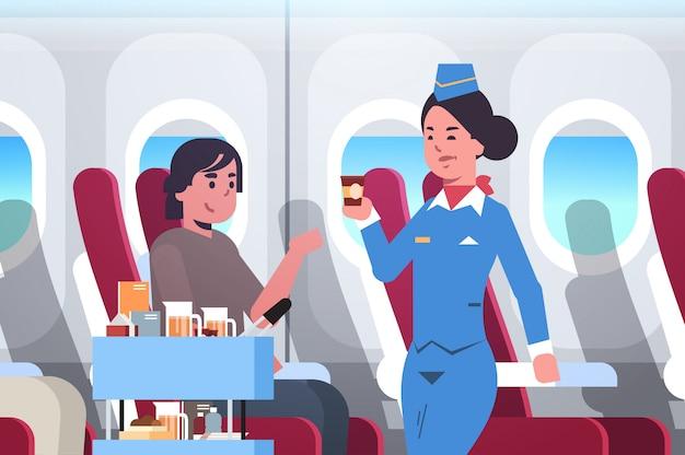 La azafata que sirve bebidas a la azafata de pasajeros en uniforme empujando la carretilla de mano servicio profesional concepto de viaje avión moderno tablero retrato interior Vector Premium