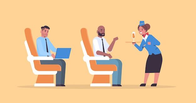 Azafata sirviendo bebidas alcohólicas a bordo del avión pasajeros azafata en bandeja de retención uniforme con copa de champán concepto de viaje de servicio profesional plano horizontal de longitud completa Vector Premium