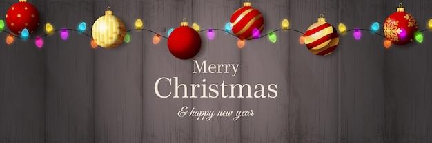 Banner de feliz navidad con bolas rojas sobre suelo de madera gris vector gratuito