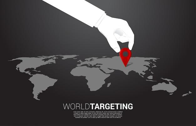 Cerrar la mano del marcador de pin de ubicación de lugar de negocios en frente del mapa mundial. concepto de máquina de aprendizaje y sistema de navegación. Vector Premium
