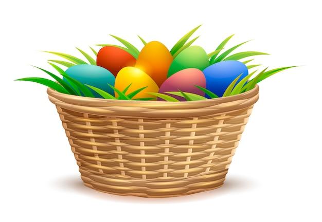 Cesta de mimbre llena de huevos de pascua en pasto Vector Premium