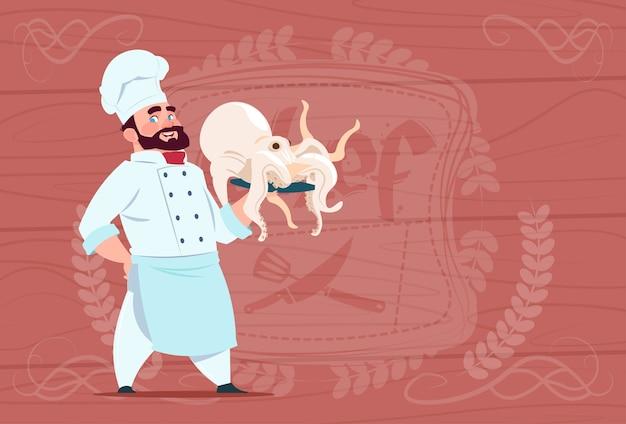 Chef cocinero hold octopus smiling cartoon jefe del restaurante en uniforme blanco sobre fondo con textura de madera Vector Premium