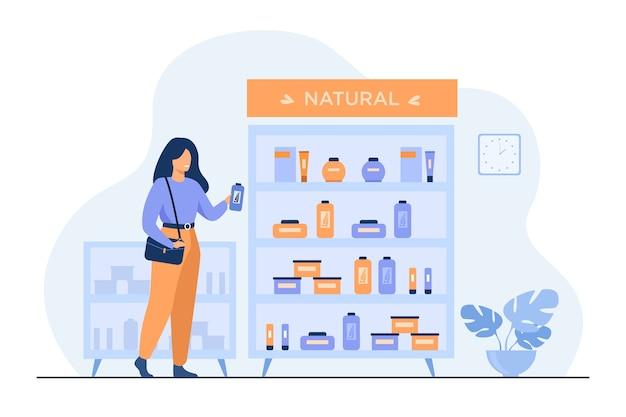 Chica eligiendo productos de belleza ecológica en la tienda de cosméticos, de pie en el estuche con cremas y lociones y tomando la botella de champú. vector gratuito