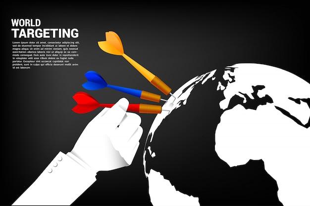 Cierre de la mano mantenga la flecha de dardo golpeó en el mundo. Vector Premium