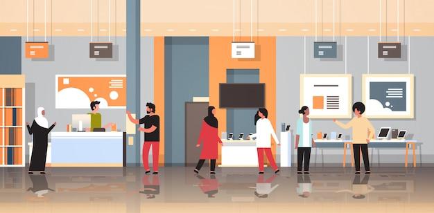 Clientes de raza mixta en la tienda de tecnología moderna visitantes interiores que eligen computadora digital portátil pantalla de televisión teléfono inteligente aparatos electrónicos mercado horizontal plana Vector Premium