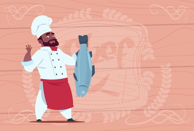 Cocinero afroamericano chef cocinar pescado sonriente restaurante de dibujos animados jefe en uniforme blanco sobre fondo con textura de madera Vector Premium