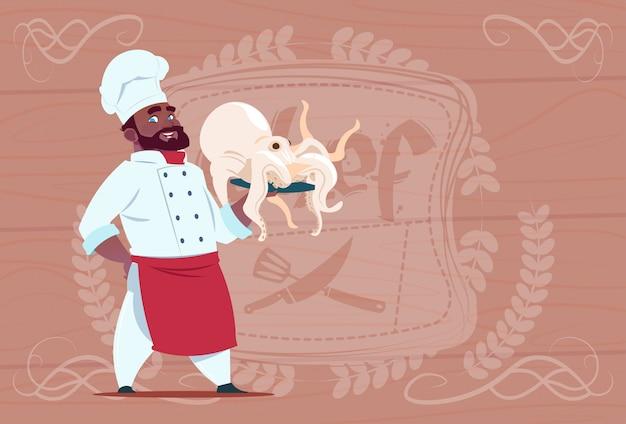 Cocinero afroamericano chef sostener pulpo sonriendo jefe de restaurante de dibujos animados con uniforme blanco sobre fondo con textura de madera Vector Premium