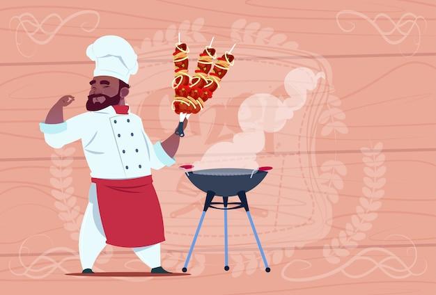 Cocinero afroamericano cocinero sostener kebab sonreír jefe de restaurante de dibujos animados con uniforme blanco sobre fondo con textura de madera Vector Premium