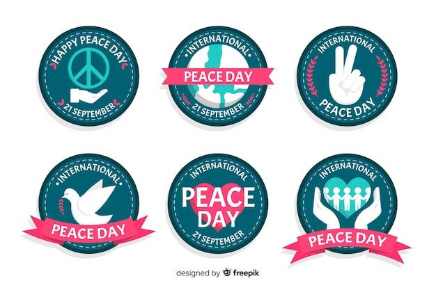 Colección de emblemas del día de la paz en diseño plano vector gratuito