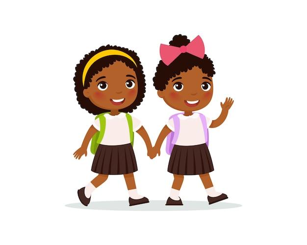 Colegialas africanas que van a la escuela ilustración plana. par de alumnos en uniforme tomados de la mano aislados personajes de dibujos animados. dos estudiantes de primaria felices con mochilas agitando la mano vector gratuito
