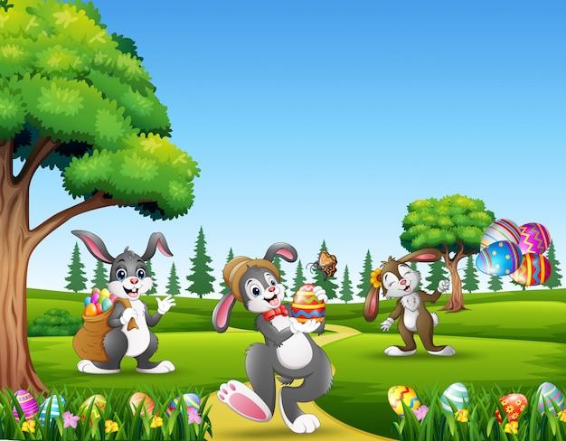 Conejitos de dibujos animados con huevos decorados sobre fondo de pascua Vector Premium