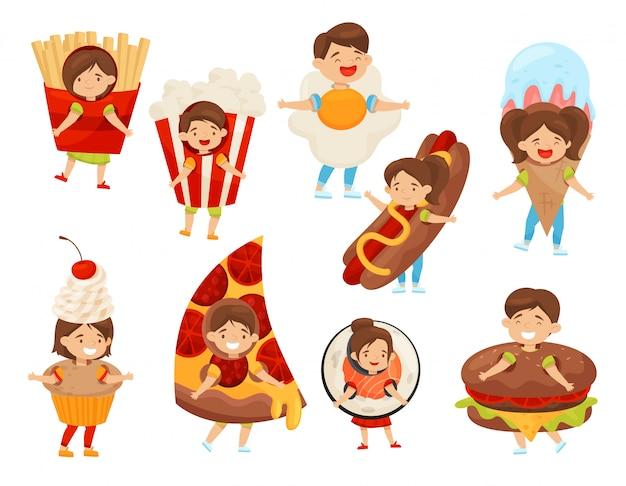 Conjunto plano de niños en trajes de comida. niños y niñas lindos con expresiones de cara feliz. niños en traje de carnaval Vector Premium