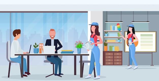 Conserjes equipo de limpieza en uniforme trabajando juntos concepto de servicio de limpieza centro de trabajo creativo centro de oficina moderno interior plano horizontal de longitud completa Vector Premium