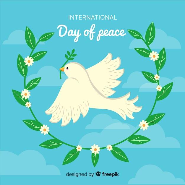 Dibujado a mano el día de la paz con paloma y hojas de olivo vector gratuito