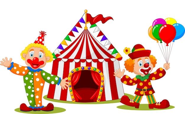 Dibujos animados de payaso feliz frente a la carpa de circo Vector Premium