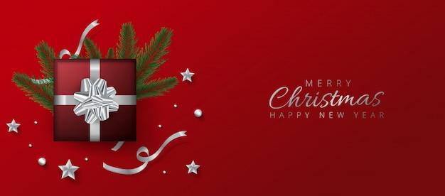 Diseño de encabezado o banner rojo decorado con caja de regalo, adornos y hojas de pino para feliz navidad y feliz año nuevo. Vector Premium
