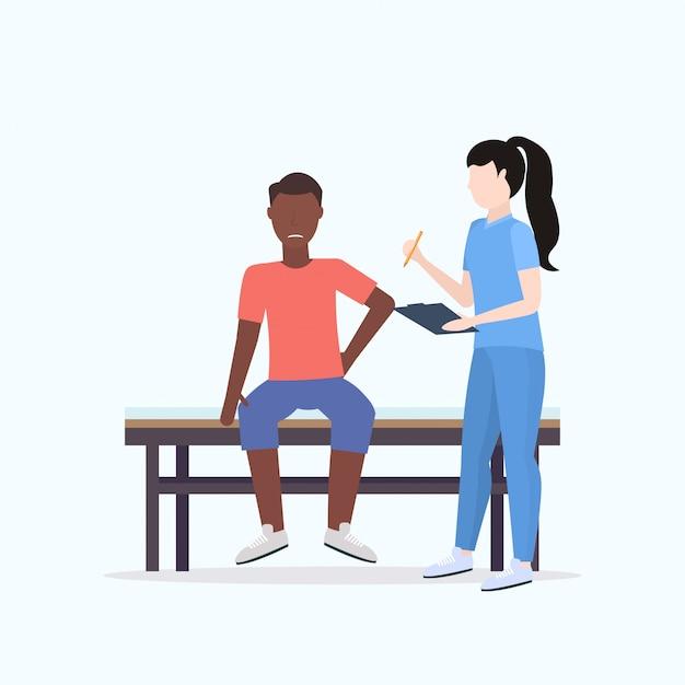 Doctor sujetando el portapapeles terapeuta consultor herido paciente masculino sentado en la cama deporte manual fisioterapia concepto de longitud completa Vector Premium