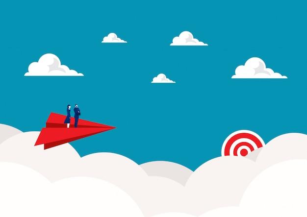 Dos empresarios de pie en avión de papel rojo volando en el cielo Vector Premium