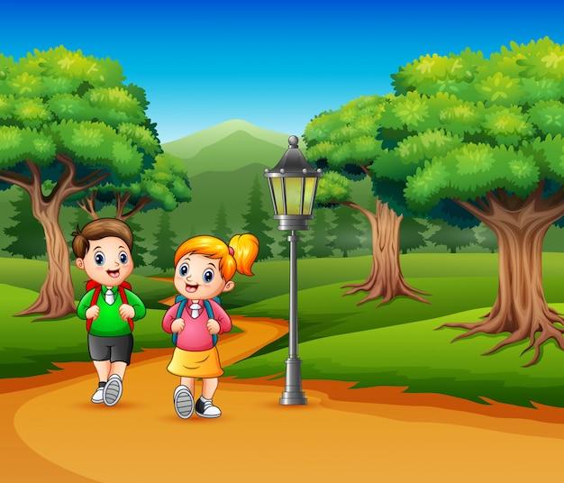 Dos escolares están caminando por la carretera un bosque. Vector Premium