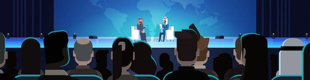 Dos hombres o políticos de negocios árabes en una conferencia o debate entrevista, entrevista hablar sobre un mapa del mundo frente a una gran audiencia ilustración horizontal Vector Premium