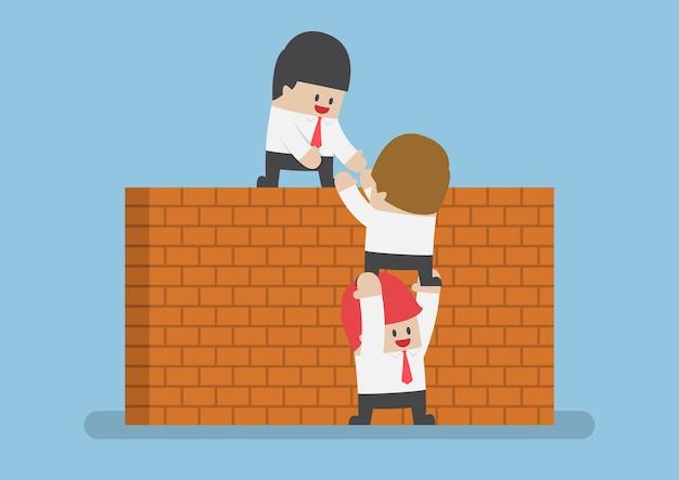El empresario ayuda a su amigo a cruzar la pared de ladrillos, concepto de trabajo en equipo Vector Premium